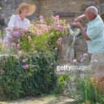 Foto mostrando avós regando jardim